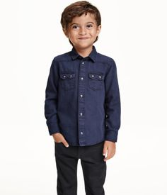 H&M CONSCIOUS. Shirt in washed denim with a turn-down collar and pointed yoke at front and back. Snap fasteners at front and chest pockets with flap and snap fasteners. Made partly from recycled cotton.