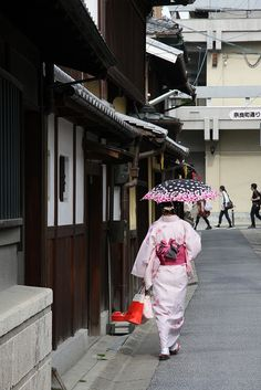 Woman wearing exquisite kimono. Even her shopping bag compliments the robe. This is why designers always get inspiration from other cultures. Look at the patterns on this kimono. Biddy Craft