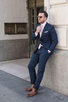 Acheter la tenue sur Lookastic: https://lookastic.fr/mode-homme/tenues/blazer-chemise-de-ville-pantalon-de-costume-bottines-chelsea-cravate--lunettes-de-soleil/4972 — Bottines chelsea en cuir brunes — Pantalon de costume bleu marine — Pochette de costume blanc — Chemise de ville rose — Cravate beige — Blazer bleu marine — Lunettes de soleil brun