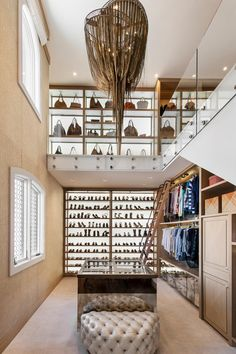 This huge, luxurious two-story walk-in closet from Angelica Henry Design features incredible amenities such as an office area, a vanity with running water, and even a combination washer-dryer unit. Filling the space are abundant custom details, such as LED-lit display shelving, artistic risers on the stairs, and even a large aquarium.