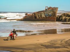 KLR650 Motorcycle playing on the beach on the Wild coast South Africa. Behind is the shipwreck the Jacaranda.