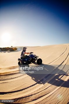 Stockfoto : Quad biker driving up sand dune on hot summer day