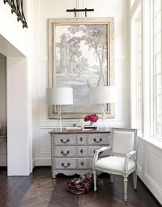 Elegant, chic french foyer design with tall ceiling, white & gray French chair, gray chest console table, glass lamps, chevron herringbone pattern wood floors and art.