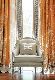 """Drapes in Chinois Palais in Tangerine trimmed with Labyrinth Tape in Dove 6"""" Wide. Pillow with Madame Wu Applique in Swan. Chair in Honeycomb in Swan."""