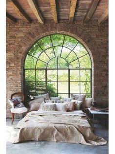 Slaapkamer met stenen buitenmuur en balkenplafond