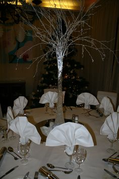 White winter centrepiece - Tall lily vase, aqua beads and lighting with white branches with dangling accents. - Cloverleaf Chair Covers