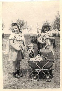 Vintage photo of children playing with dolls circa 1950's. Love the make believe capes the girls' are wearing!