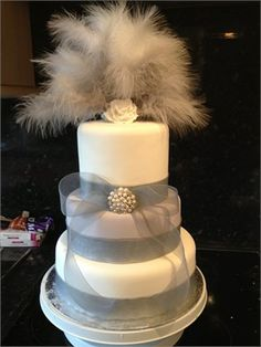Grey and white cake decorated with silver grey ribbon and diamante and pearl brooch topped with grey feathers