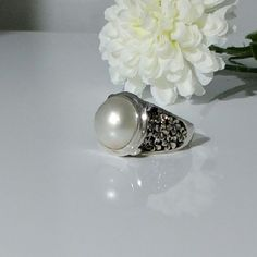 NEW LISTING  White Mabe Pearl Ring A floral pattern surrounds an impressive 12.5mm bezel set, white mabe cultured pearl. The floral detailing along each side of the ring produces an attractive contrasting shadow effect. This size 8 sterling  silver ring is striking and substantial (8 grams tw). The pearl treatment is bleached. New.  Measurements and weights are approximate. Photos may be enlarged to show detail. Jewelry Rings