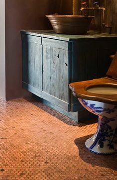 bathroom floor covered in pennies, copper bucket vessel sink, exposed copper pipe faucet, hand painted toilet from France with wood seat