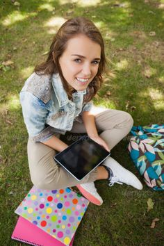 Pretty cheerful student sitting on grass using tablet on campus at college ... Looking At Camera, attractive, beautiful, book, book bag, campus, casual, caucasian, cheerful, college, digital tablet, female, grass, green, happy, learning, leisure, notebook, notepad, outdoors, portrait, pretty, reading, revising, sitting, smiling, student, studying, tablet, tablet computer, tablet pc, textbook, touchscreen, university, using, woman, young adult