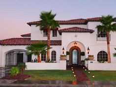 The exterior of this traditional Spanish-style home has a brick walkway, an arched entryway and a red tile roof. Landscape lighting illuminates the entry to the home and iron gate details can be seen on the left.