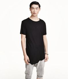 Long T-shirt in ribbed jersey with raw edges, seam at back, and asymmetric hem.