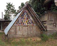 Une maison aluku de Loka (hameau de Papaïchton). Le remplissage du pignon en planches découpées, ajourées et peintes comporte en son centre le motif Kelewa qui représenterait le corps féminin, la porte est sculptée d'un motif d'entrelacs dit tembé, peu visible sur cette photo. A droite et derrière, des constructions contemporaines. Phot. Inv. M. Heller © Inventaire général, ADAGP, 2001.