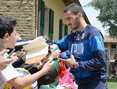 Leonardo Bonucci of Italy sign autographs for fan after a training session at Coverciano on May 27, 2014 in Florence, Italy.
