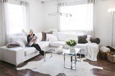 olohuone,sohva,sohvanurkkaus,vaaleat sävyt,tumma parketti,talja,torkkupeitto,sisustustyynyt,valkoinen,kattovalaisin,lasipöytä,sohvapöytä,koriste-esineet,kori,valoisa,avara,vaalea,verhoilu,verhot,kukat,skandinaavinen