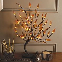 Perfect for adding a stylish element to any desktop, this exquisite decorative tree stands 22 tall and features meticulously wrapped branches in an earthy brown hue, plus beautiful amber-colored leaves accented by 56 warm white LED lights.