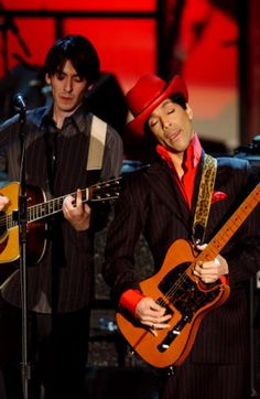 Dhani  Harrison in background (George's son) as Prince joins in a song at the 2004 Rock and Roll Hall Of Fame induction ceremony. Harrison and Prince were