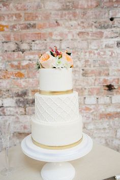 Three Tier White Wedding Cake Topped with Flowers | Brides.com