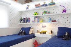 Este quarto de 8m² possui prateleiras em todas as paredes e camas com gavetões para armazenar o que não cabe dentro do armário.