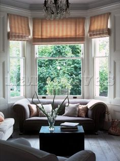 Living room with chesterfield sofa and large sash window with roman blinds