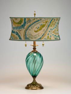 Lucia by Susan Kinzig and Caryn Kinzig. Vibrant aqua blown glass, oval shade with soft abstract design with turquoise and green colors. Beaded pulls and finial. Uses two 60-watt maximum bulbs (40-watt bulbs included).