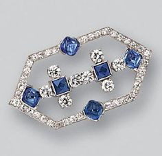 SAPPHIRE AND DIAMOND BROOCH, CARTIER, CIRCA 1925. The elongated hexagonal motif decorated with 4 sugarloaf cabochon sapphire and 2 French-cut sapphires, completed by 8 round and 38 single-cut diamonds weighing approximately 1.50 carats, mounted in platinum, signed Cartier