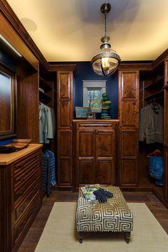 Elegante dunkle Holz begehbarer Kleiderschrank mit Senf gelb Decke und osmanischen auf passenden dunklen Holzböden.