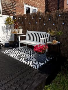 black deck with white bench and festoon lighting