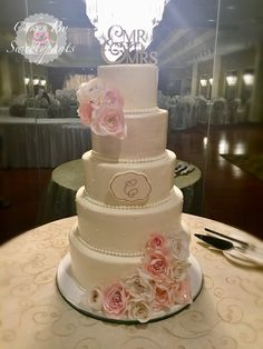 Ivory/Blush tiered, wedding cake.  Ivory and blush wafer paper roses. Edible monogrammed plaque.