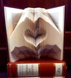 Hartje gevormd door twee handen gevouwen in een boek.        DIY Tutorial op boekvouwen . nl