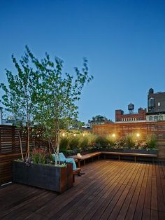 The warm hues of Ipe wood and lush garden planters create an intimate outdoor setting at dusk in this urban deck design.