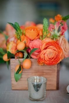 Orange flowers in a wood planter; gorgeous on tables at the reception, on the bridal table, the cake table, or anywhere you want a floral arrangement. (photographed by Troy Grover Photographers)