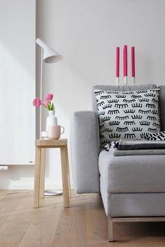 Fein dosierte Farbe: Tulpen und Kerzen in frischem Pink. Ein schlichtes graues Sofa und die tolle Louis Poulsen Stehleuchte
