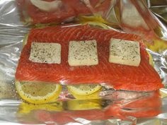 Preheat the oven to 300 degrees.  Place 4-6 lemon slices on each sheet of foil. Lay Salmon fillet on top of lemon.  Place butter on top of fish and season with salt and pepper.  Fold foil into a bag (or pouch if you like that better) and seal.  Cook for about 25 minutes.