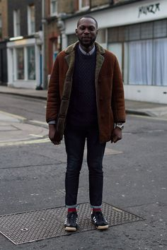 Coggles Fashion - London Street Style with oversized sheepskin jacket, buttoned up light blue shirt, navy blue knit jumper, dark denim turn up jeans, red socks, large silver watch and black leather sneakers. #streetstyle #menswear #fashion