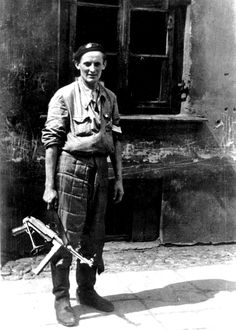 """Polish Resistance fighter Roman """"Rom"""" Marchel stands with a captured German MP-40 submachine gunina barricade on Ciepła Street during the Warsaw Uprising. Marchel belonged to aunit which was defending the Polish Mint. Warsaw, Poland. 20 August 1944."""