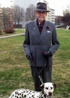 Acheter la tenue sur Lookastic:  https://lookastic.fr/mode-homme/tenues/blazer-croise-chemise-de-ville-pantalon-de-costume-chapeau-cravate--echarpe-gants/2153  — Blazer croisé à rayures verticales gris foncé  — Chapeau gris foncé  — Pantalon de costume à rayures verticales gris foncé  — Pochette de costume en soie blanc  — Écharpe écossais bordeaux  — Gants en cuir noir  — Chemise de ville blanc  — Cravate bordeaux