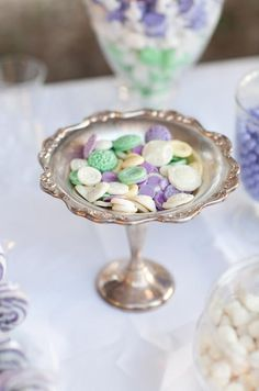 A silver bowl of The Frosted Petticoat's Chocolate Buttons in feminine tones of lavender, white and mint green is a lovely accent to a dessert table.