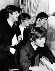 The Beatles wave to fans assembled below their Plaza Hotel window after they arrived in New York City on Feb. 7, 1964 for a short tour of the United States. From left to right are, Paul McCartney, Ringo Starr, John Lennon, and George Harrison.