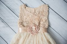 This dress is just beautiful! It includes a dark cream rosette top with a flowy bottom and lace trim on the bottom. It also has a single flower sash that is removable. Perfect for your next special event. IDEAL WEAR: Flower Girl Dress Cake Smash First Communion Photography Prop Bridesmaid dress Paired with Cowboy boots Baptism Tea Party Birthday Rustic theme Wedding First Birthday   Size..... Chest.....Length (Shoulder to Hem) 2T.........10.5in........22in 3T.........11in...........23in…