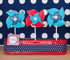 Patriotic Pinwheel Cookie Pops ~ The cookies were stuck into long glass containers that we filled with red M & Ms and had a thick navy/white ribbon wrapped around