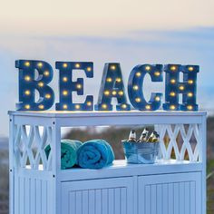 """""""Beach"""" isn't just a state of mind-it's a marquee sign that continually reminds you that's where you want to be. Outdoor decor sign features 42 warm-white LEDs spread throughout the ocean-inspired, aqua-colored word. Place these marquee letters on any flat surface or mount them using the keyholes in back."""