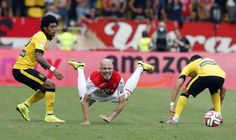 Monaco's Andrea Raggi (C) falls as he is challenged by Lille's Isaac Ryan Mendes (L) during their French Ligue 1 soccer match at Louis II stadium in Monaco, August 30, 2014. REUTERS/Eric Gaillard