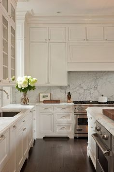 Love all of the bright white in this kitchen. The gold light fixture and wooden chairs really pop.   Interior Design Pro