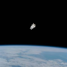 Spacewalking astronaut on untethered spacewalk surrounded by empty space with Earth below