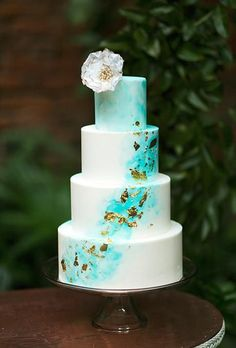 143403a5ab348b A four-tiered white wedding cake with blue-and-gold details by