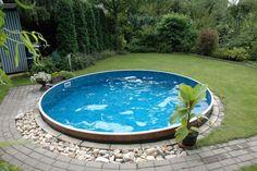 construire sa piscine extérieure de forme ronde entourée de galets décoratifs et pierres naturelles