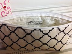 Classic design quatrefoil, of 100% cotton fabric, in timeless colors of white and black. Padded, and fully lined with gray and white baby's breath fabric.  The shape of the case is sleek with curved corners at the top towards the zipper for a secure side-to-side closing. The bottom of the case has a flat bottom that allows it to stand on its on.