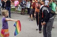 Dieses kleine Mädchen stellt sich mit einer Regenbogen-Flagge gegen einen tobenden Prediger